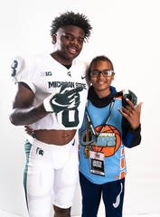 Mansfield Senior's Angelo Grose (left) poses with his little brother, Jaiden Grose, who is battling Leukemia, during a photo shoot where Angelo made his commitment to play college football at Michigan State University.