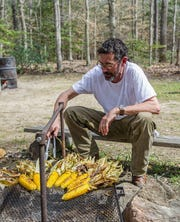 Cool Smoke pitmaster Tuffy Stone tends to corn on the grill.