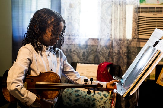 Caesar Sant adjusts his music stand while practicing violin, June 25, 2019. Sant was born with sickle cell anemia and at five years old experienced 3 strokes that temporarily paralyzed him. At two-years-old Sant began learning to play the violin, and by four-years-old he played the National Anthem at baseball games.