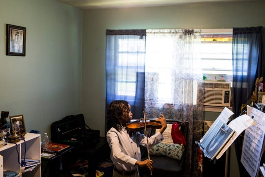 Caesar Sant practices with his violin at home in Memphis, June 25, 2019. Sant was born with sickle cell anemia and at five years old experienced 3 strokes that temporarily paralyzed him.