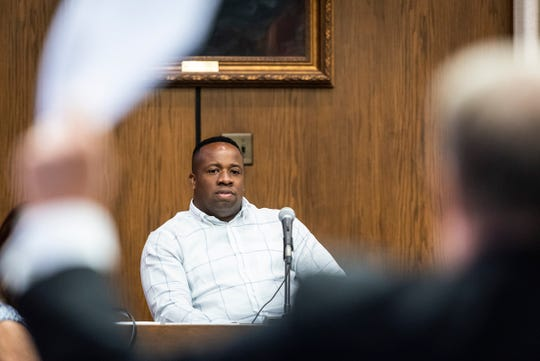 In this Monday, June 24, 2019 photo, rapper Yo Gotti, whose legal name is Mario Mims, looks on as attorney Clarke Dummit waves Yo Gotti's affidavit during a hearing in Winston-Salem, N.C.  A North Carolina judge is refusing to throw out a $6.6 million judgment against the rapper. Singer Young Fletcher's manager Michael Terry filed a lawsuit accusing Mims of shirking a $20,000 deal to rap on one of Young Fletcher's songs and thereby boost sales. Terry says Mims didn't sign paperwork necessary for putting the song on streaming services.