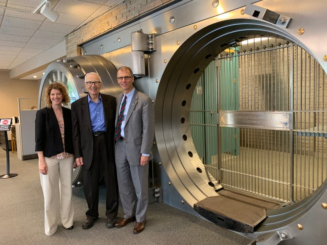 Waukesha State Bank officials (from left) Stephanie Ohlfs, vice president of marketing; Ty Taylor, president; and Don Taylor, past president, stand in front of the historic vault inside the bank's main location in downtown Waukesha. The vault, purchased from an Iowa bank in the 1960s, cost $25,000 to ship by truck. It remains an iconic element in the bank, built in 1956.
