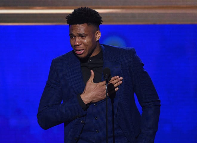 The Bucks' Giannis Antetokounmpo is in tears as he delivers his acceptance speech.