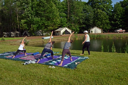 Glampers practice yoga near their glamping tents at The Fields in South Haven, Michigan.