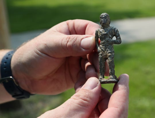 Jim Walters shows the kind of neat things one can find magnet fishing like this toy soldier.