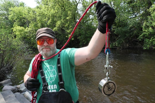 Jim Walters of West Bend uses his powerful magnet to go fishing for metal objects in the Milwaukee River in West Bend.  Attached to a coil of rope he throws it out as far as he can.  Then it drags across the bottom of river as he pulls it in.