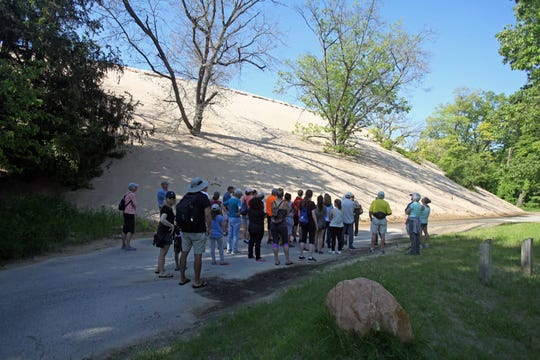 A ranger speaks to a group of visitors at the base of Mount Baldy in Indiana Dunes National Park on June 7, 2019. The dune is closed to visitors except on ranger-led hikes.