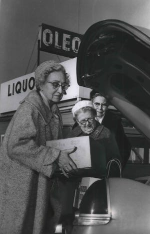 Members of the Wisconsin Federation of Women's Clubs load up the car with cases of yellow oleomargarine outside an Illinois supermarket near the Wisconsin-Illinois border. They stocked up because colored margarine was banned in Wisconsin. This photo was published in the Dec. 23, 1964, Milwaukee Sentinel.