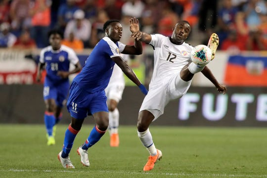 Costa Rica forward Joel Campbell (12) tries to get a foot on the ball while challenged by Haiti midfielder Derrick Etienne during the first half of a CONCACAF Gold Cup soccer match, Monday, June 24, 2019, in Harrison, N.J. (AP Photo/Julio Cortez)