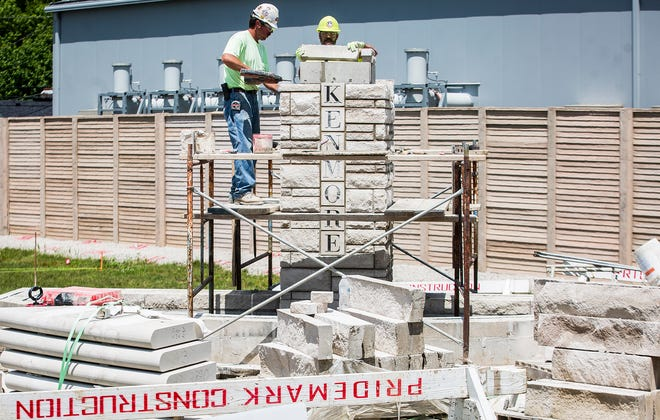 A construction crew continues work on an entrance to the Kenmore neighborhood off of Tillotson and University Avenues Tuesday, June 25, 2019.