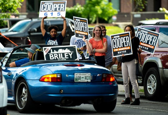 Supporters of at-large Council member John Cooper cheer as a supporter of Mayor David Briley drives past before a mayoral debate at Belmont University's McAfee Concert Hall in Nashville, Tenn., Tuesday, June 25, 2019.