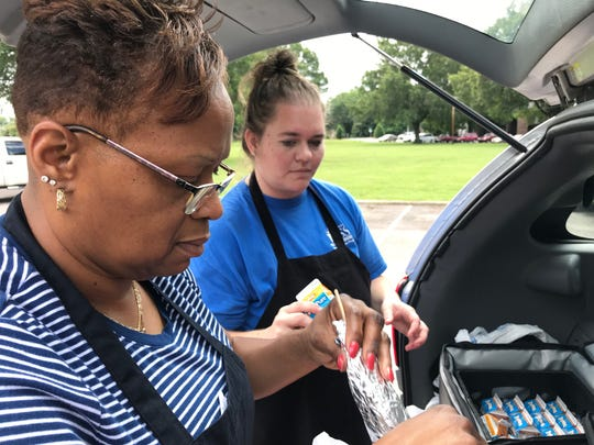 Gail Campbell and Tiffany Thompson, child nutrition staff members at Franklin Special School District, pack lunches as children line up behind them in the Cadet Park area.