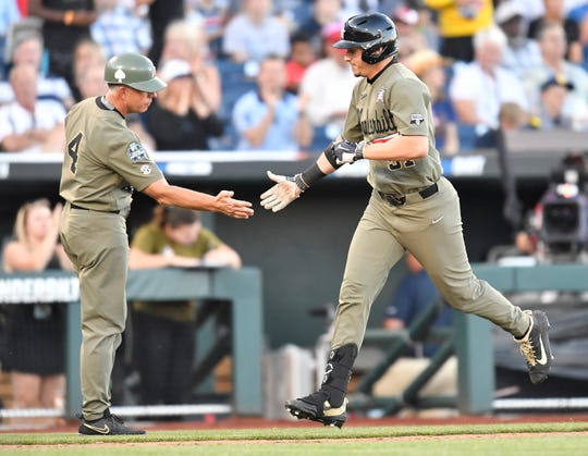 Vanderbilt coach Tim Corbin congratulates J.J. Bleday (51) on his home run in the bottom of the sixth inning against Michigan in Game 1 of the College World Series Finals.