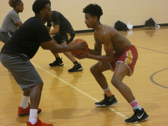 New Licking Heights coach Shaun Fountain works with Judah Spears on a defensive shuffle drill during a recent practice.