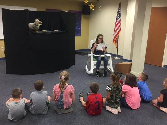 Clyde the Coyote and storyteller Stephanie Anthony entertain children at a June 24 Granville Public Library event. The library is planning to add some Sunday hours starting in September.