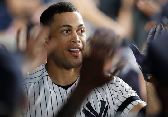 Teammates congratulate New York Yankees' Giancarlo Stanton after he hit a three-run home run during the sixth inning of a baseball game against the Toronto Blue Jays, Monday, June 24, 2019, in New York. (AP Photo/Kathy Willens)