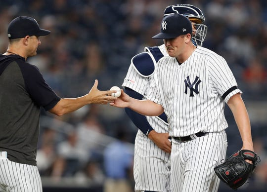 New York Yankees manager Aaron Boone, left, takes the ball from relief pitcher Jonathan Holder after Holder gave up five runs to the Toronto Blue Jays in the eighth inning of a baseball game, Monday, June 24, 2019, in New York. (AP Photo/Kathy Willens)