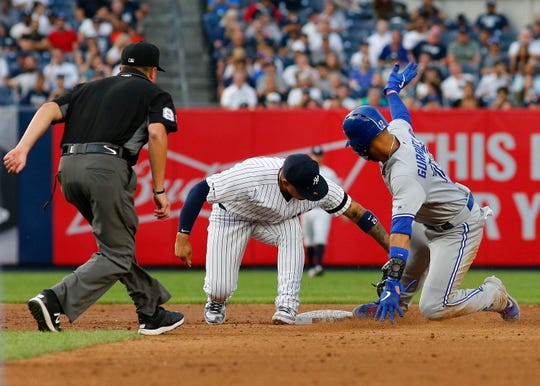 Toronto Blue Jays left fielder Lourdes Gurriel Jr. (13) is tagged out by New York Yankees second baseman Gleyber Torres (25) attempting to steal second base during the third inning at Yankee Stadium.