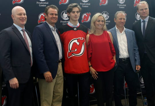 Devils Head Coach, John Hynes is shown on the far left as Jim and Ellen Hughes surround their son, Jack Hughes (wearing jersey), Managing Partner, harris Blitzer Sports & Entertainment, Josh Harris, and President of the Devils, Hugh Weber pose for a photograph during a press conference, Tuesday June 25, 2019.
