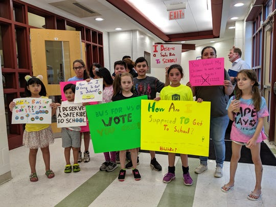 Students and parents hold up signs at the Saddle Brook school board meeting on June 25 protesting a cut to courtesy busing.