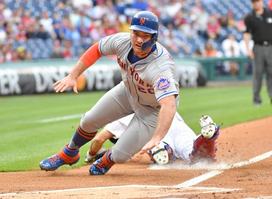 New York Mets first baseman Pete Alonso (20) reaches for home plate as he scores a run during the first inning against the Philadelphia Phillies at Citizens Bank Park.