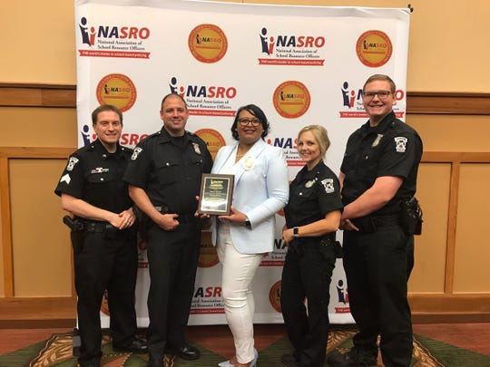 Monica Merritt (center) accepted an award from the National Association of School Resource Officers.
