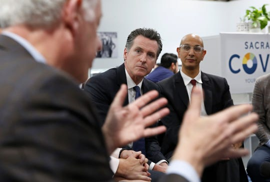 Gov. Gavin Newsom, center, listens May 14, 2019, as John Arensmeyer, founder and CEO of Small Business Majority, left, discusses the problems small businesses have getting health insurance during a discussion with small business owners in Sacramento.