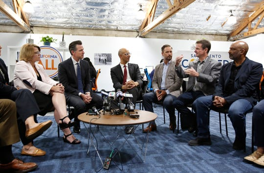 Jim Holifield, second from right, who is semi-retired and runs his own part-time consulting firm, describes the problems of getting health insurance to Gov. Gavin Newsom, second from left, May 14, 2019, during a discussion in Sacramento about health care with small business owners.