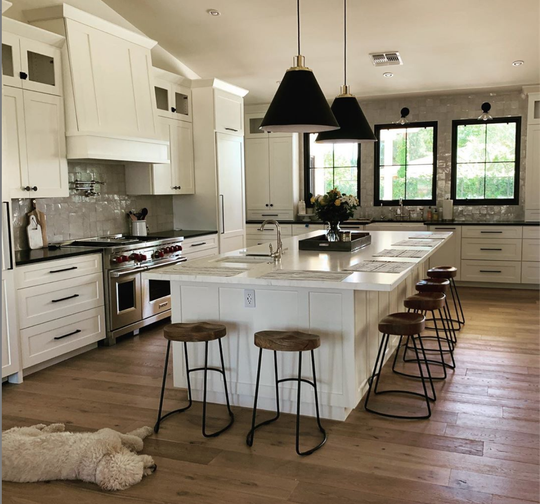 The kitchen, loved by the family dog, features extensive storage, a pot filling faucet and modern fixtures.