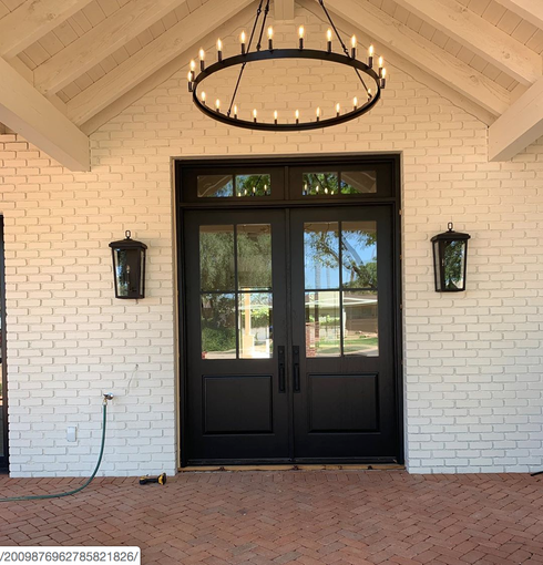 The home's symmetrical entrance is set off with a sizable candlelit chandelier.