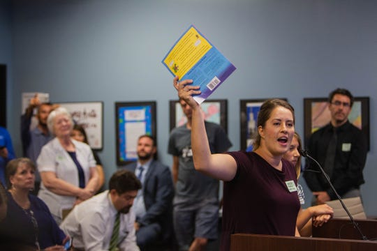 Chrisine Sbacea holds up a book to protest possible changes in sex education guidelines in public schools at a meeting earlier in June.