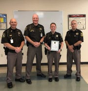 From left to right, Captain Mat King, Sheriff Donnellon, Deputy Stacie Miller and Undersheriff Matt Paulus stand while Miller is recognized with a department Lifesaving Award.