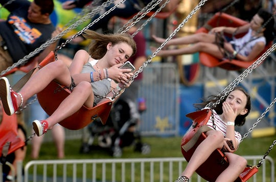 Sophia Stewart, 14, left, tries to get a photo of her friend Colette McMahon, 13, both of New Freedom, while riding the Swinger at the Shrewsbury Fireman's Carnival Monday, June 24, 2019. The carnival, featuring live music nightly, runs through June 29. It opens at 5:30 each day. Bill Kalina photo