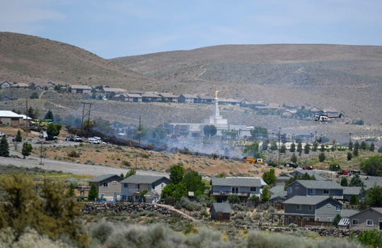 Smoke is seen billowing from a hillside near the Reno Nevada Temple in northwest Reno on June 25, 2019.