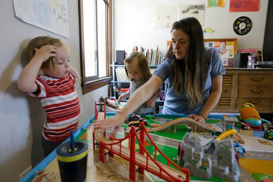 Sarah Montoya plays with her twins Farallon, left, and Nicasio, center, at their home in San Francisco.