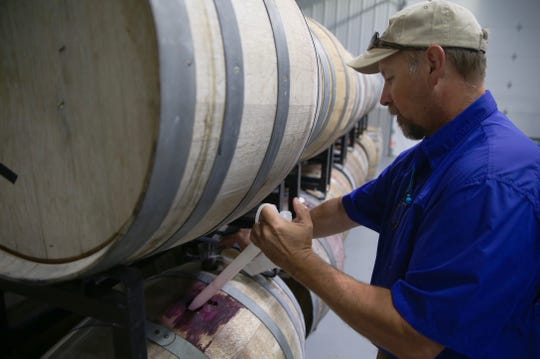 Bart Neff takes a sample of wine from a barrel in a storage facility at the Christoval Vineyard and Winery south of San Angelo on Thursday, June 20, 2019.