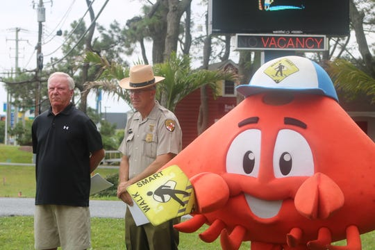 From left: Ocean City Mayor Rick Meehan, Lt. Earl Starner of the Maryland State Police and Cheswick the Crab stand at the ground breaking of a new pathway in West Ocean City on June 25, 2019.