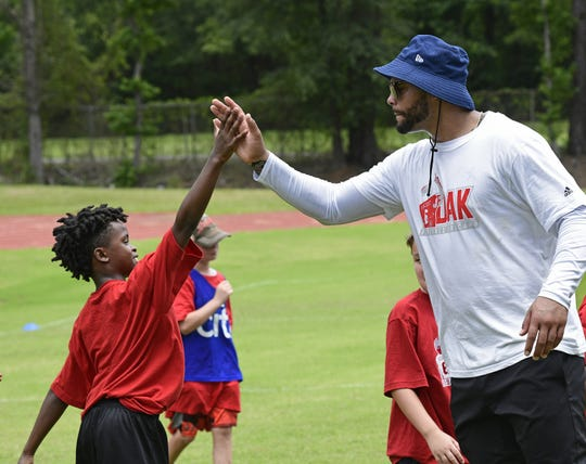 Dallas quarterback Dak Prescott high fives a youngster during his 2nd annual football camp Tuesday in his hometown of Haughton.