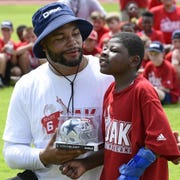 Dallas Cowboys quarterback Dak Prescott works with a young man during his ProCamp Tuesday at Haughton High School.