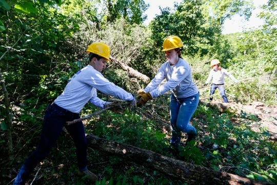 Watershed Conservation Corps crew members Morgan Wetzel (left), Hannah Alkier (center), and Tory Lydy move branches from a felled cedar tree at Wilson's Creek National Battlefield on Tuesday, June 25, 2019.