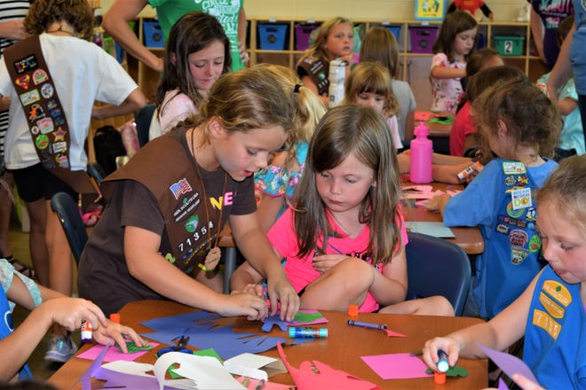 Samantha Hodge helping one of the new Daisies, Lily Rosenfelder, with her Girl Scout Promise project.