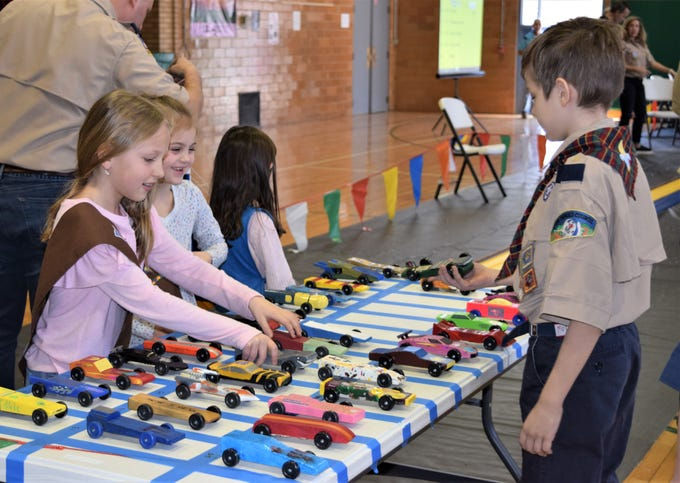 Micheala Krueger and Harper Lashmet acting as pit crew for the St. Agnes Pinewood Derby. Troop 71354 out of Hickory Hills Elementary has joined them for this event for last four years, and the girls also get to build and race cars.