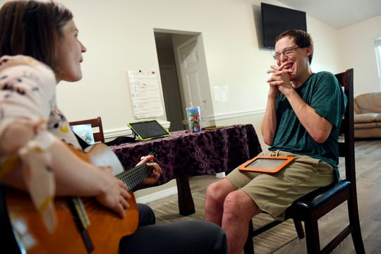 "Michael Tunic, 19, shares a laugh with Moreen Burkart, a music therapist with the Visiting Nurse Association, as she conducts her weekly session on Friday, June 21, 2019, in Tunic's Indian River County home. Tunic, who has autism, meets with Burkart to work on his verbal, cognitive and hand-eye coordination with the aid of music. ""I've been working with Michael about six to eight months now, and we mostly work on anything that's going to help him be more independent,"" said Burkart."