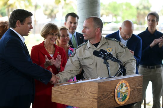 Florida Gov. Ron DeSantis (left) shakes the hand of Col. Curtis Brown of the Florida Fish and Wildlife Conservation Commission, during a news conference on Tuesday, June 25, 2019, at the Florida Oceanographic Coastal Center in Stuart. DeSantis signed a bill that would transfer enforcement of environmental crimes from FWC to the Department of Environmental Protection.