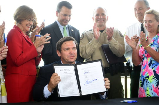"""Surrounded by supporters, Florida Gov. Ron DeSantis holds up a newly signed bill that will transfer primary powers and duties of the Fish and Wildlife Conservation Commission relating to certain environmental crimes and the enforcement of related laws to the division of law enforcement within the Department of Environmental Protection on Tuesday, June 25, 2019, at the Sea Turtle Pavilion at the Florida Oceanographic Coastal Center in Stuart. """"It made sense that the agency who is primarily in charge of protecting our natural resources would be the one where you have the criminal enforcement,"""" DeSantis said."""