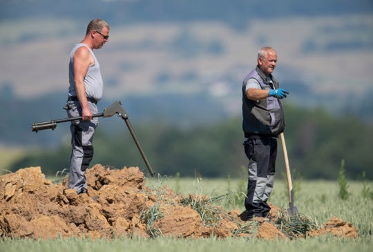 Workers inspect a big crater on a corn field after a bomb from the World War exploded in Halbach, Germany, Monday, June 24, 2019. The bomb must have stayed under the corn field since the World War until the chemical detonator reacted in the end. No one was injured. (Boris Roessler/dpa via AP)