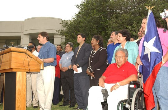 In this 2003 file photo, Texas State Rep. Jim Dunnam opens the press conference at the Ardmore Holiday Inn. The 51 Texas Democratic representatives stand behind him with Paul Moren of El Paso in the wheelchair and Gabi Canales of the South Texas counties in District 35 holds the Texas State flag. Photo by Harry Tonemah