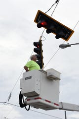 A worker with the City of Zanesville repairs a stop at the intersection of Maple Avenue and Bell Street. Storms in Muskingum County caused extensive tree and power line damage on Monday evening.