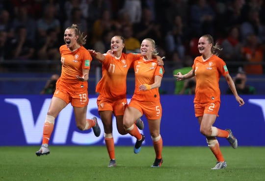 Dutch players celebrate after scoring the goal-ahead goal against Japan to give Netherlands a 2-1 win.