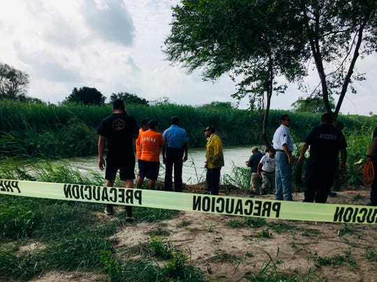 Authorities stand behind yellow warning tape along the Rio Grande bank where the bodies of Salvadoran migrant Oscar Alberto Martínez Ramírez and his nearly 2-year-old daughter, Valeria, were found in Matamoros, Mexico, on June 24, 2019. They drowned trying to cross the river to Brownsville, Texas. Martinez's wife, Tania, told Mexican authorities she watched her husband and child disappear in the strong current.